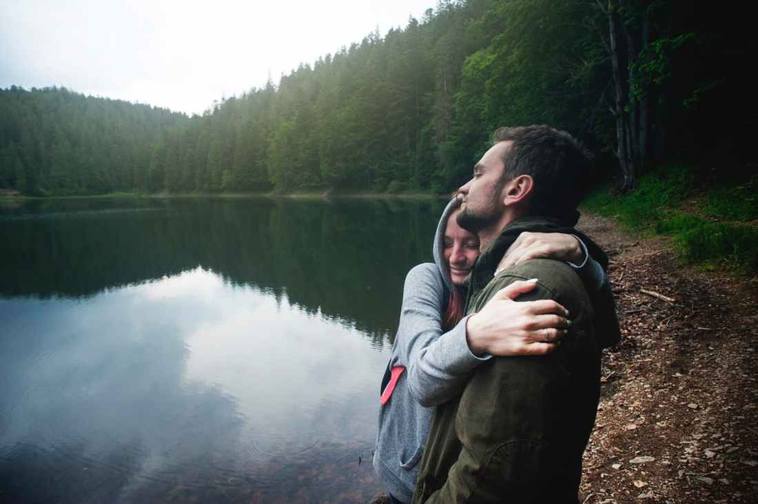 woman hugging man standing beside body of water
