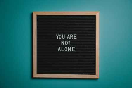 you are not alone quote board on brown wooden frame